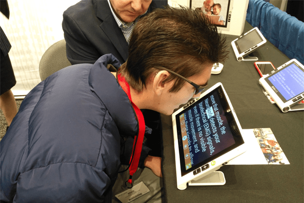 Visitor trying text to speech function of Zoomax Snow 10 Pro video magnifier at ATIA 2018 conference